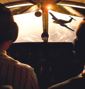 Pilots look out a plane windshield at a small plane flying towards them